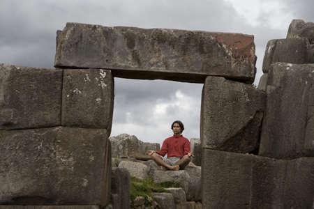 incan: Un giovane uomo medita in antiche rovine Inca di fuori di Cuzco, Per�  Archivio Fotografico