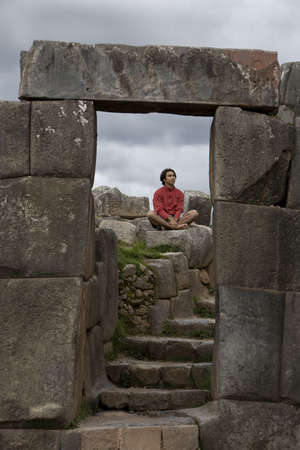 peruvian ethnicity: A young man meditates in ancient Incan ruins outside Cuzco, Peru Stock Photo