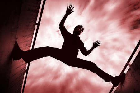 thirtysomething: Man stretching between two walls Stock Photo