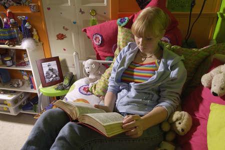 belief systems: Ragazza leggendo la Bibbia nella camera da letto  Archivio Fotografico
