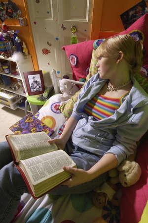 foto: Meisje het lezen van de Bijbel in de slaap kamer