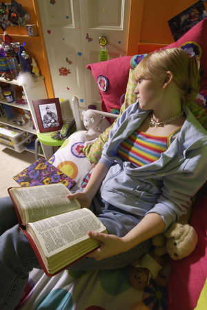 one teenage girl only: Muchacha leyendo la Biblia en el dormitorio