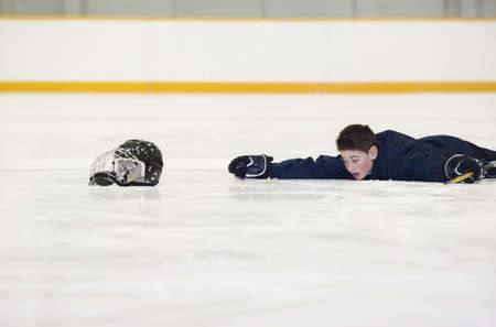 Hockey player who has fallen on the ice photo
