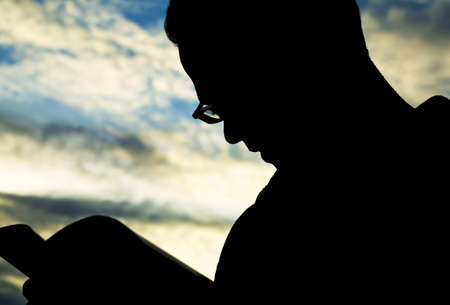 bookish: Silhouette of man reading Stock Photo
