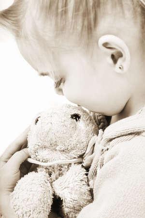 sepias: Child holding soft toy