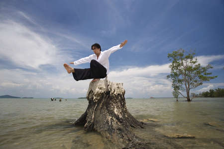 belief system: A man balancing on a tree stump on a beach in Koh Lanta,Thailand Stock Photo