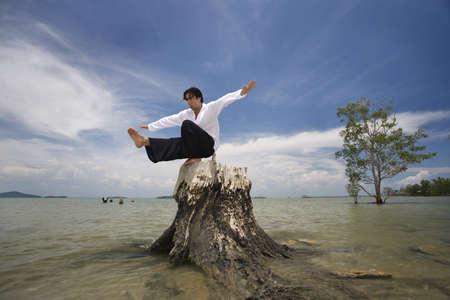 belief systems: Un uomo di bilanciamento su un ceppo di albero su una spiaggia in Thailandia Koh Lanta