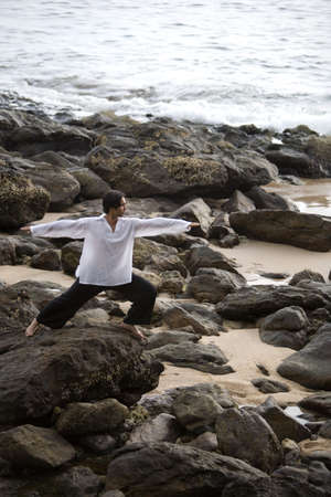 something athletic: A man stretching on a rocky beach in Koh Lanta,Thailand