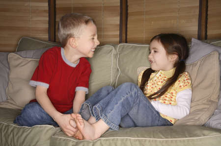 Boy and girl playing on a couch photo