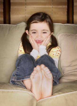 giggling: Girl sitting on a couch