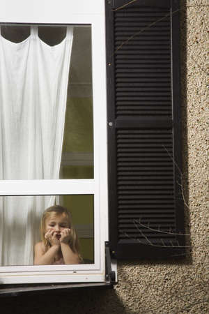 A girl looking out a window Stock Photo - 7208369