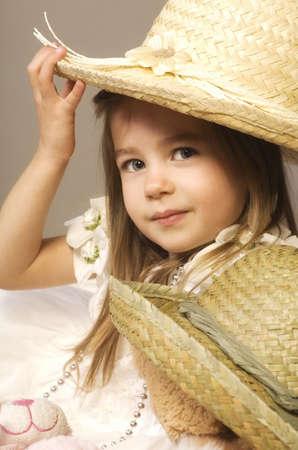 Girl and teddy bear wearing straw hats photo