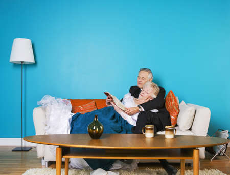 sixty something: Senior couple reading on the couch together Stock Photo