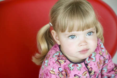 high angles: Little girl sitting on a red chair