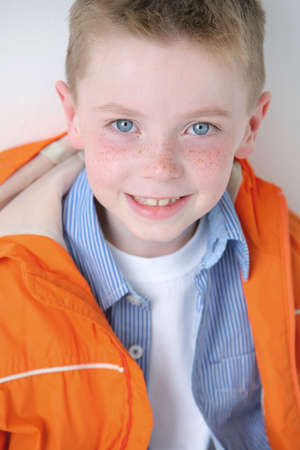 Young boy with freckles smiling at camera Banco de Imagens