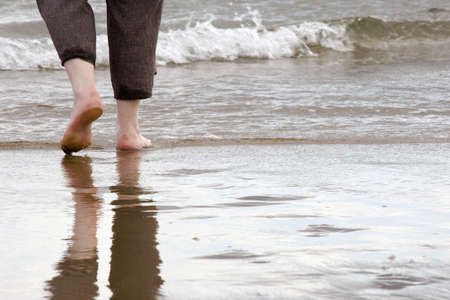 water's edge: Person walking barefoot on the beach