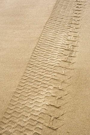 traces pneus: Pistes de pneu dans le sable.