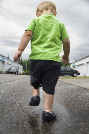 children  play: Boy walking in a puddle
