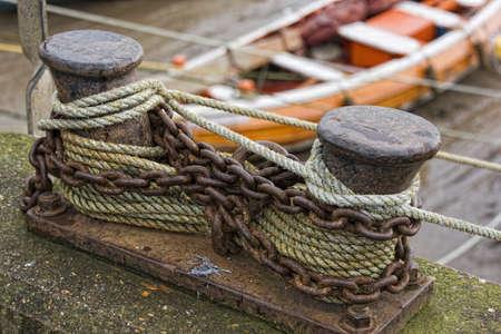 mooring bollards: Rusty chains around bollard