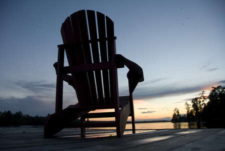 Lake of the Woods, Onta, Canada; Empty deck chair on a pier next to a lake Stock Photo - 7551537