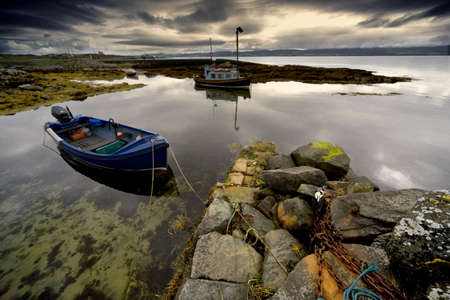 Islay, Scotland; Two boats anchored by a beach