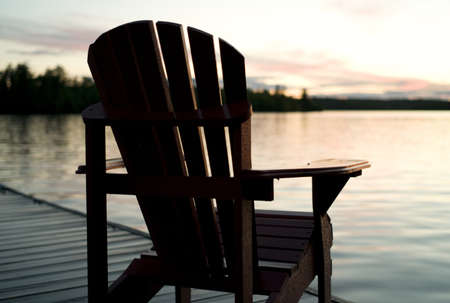 Lake of the Woods, Onta, Canada; Empty deck chair on a pier next to a lake Stock Photo - 7551480