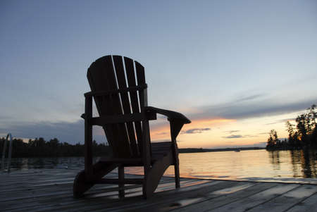 levit: Lake of the Woods, Ontario, Canada; Empty deck chair on a pier next to a lake