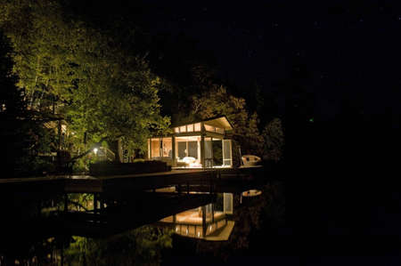 Cottage lit up at night, Lake of the Woods, Ontario, Canada Foto de archivo