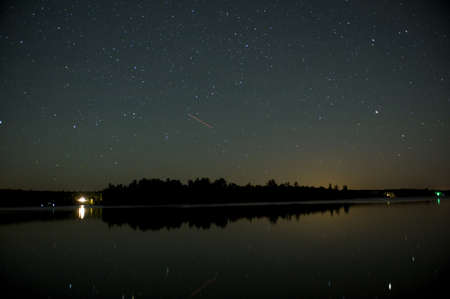 Cottage on shoreline lit up at night, Lake of the Woods, Ontario, Canada Stock Photo - 7551634