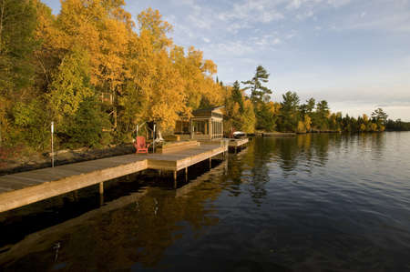 Cottage dock and autumn foliage, Lake of the Woods, Ontario, Canada Фото со стока