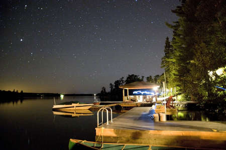 Cottage dock lit up at night, Lake of the Woods, Ontario, Canada