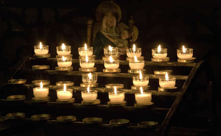 lit image: Many candles lit in front of the statue of Mary and baby Jesus LANG_EVOIMAGES