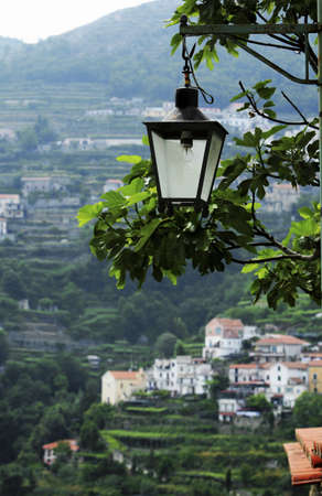 Ravello, Italy; Lantern hanging with countryside behind