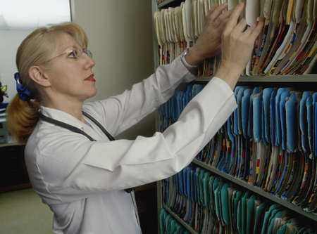 Doctor or nurse looking for patients records Imagens