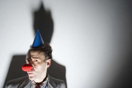 comedian: Man wearing clowns nose and hat LANG_EVOIMAGES
