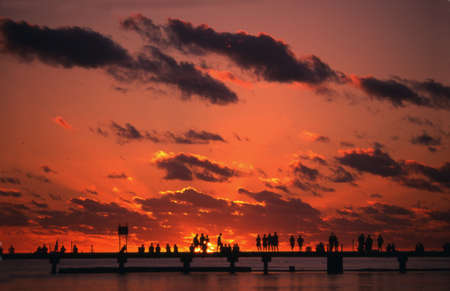 People silhouetted against an orange sunset