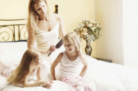 bedroom: Mother brushing daughters hair LANG_EVOIMAGES