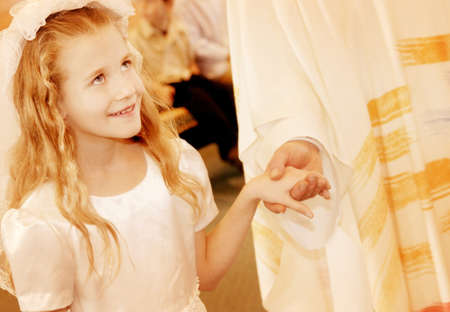 Child holds priests hand during first communion