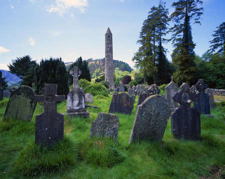 Old gravestones and tower of St. Kevin's Church, historic Glendalough Monastery Фото со стока