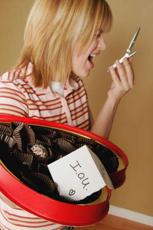 A teenage girl upset over a box of empty chocolates Stock Photo - 7551550
