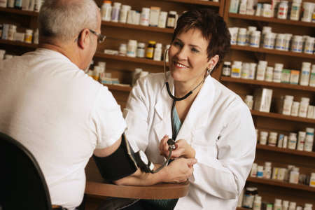 Pharmacist taking patient' s blood pressure Stock Photo - 7551616