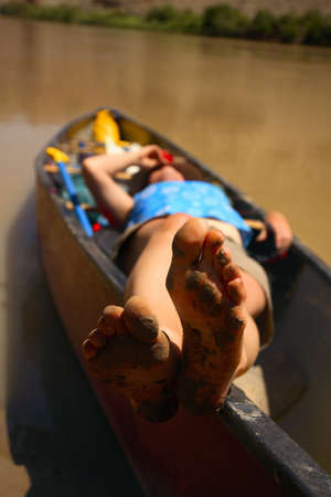 Muddy feet, relaxing in the canoe