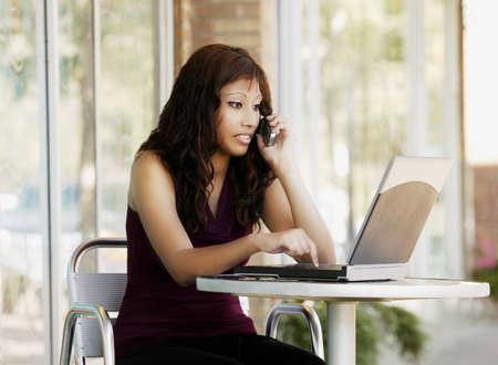 ノート パソコンと携帯電話で話している女性