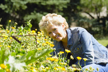 old people: Woman in flower garden LANG_EVOIMAGES