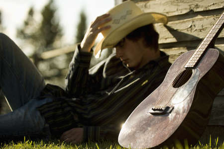 Young man wearing cowboy hat sleeping against exterior of building with guitar
