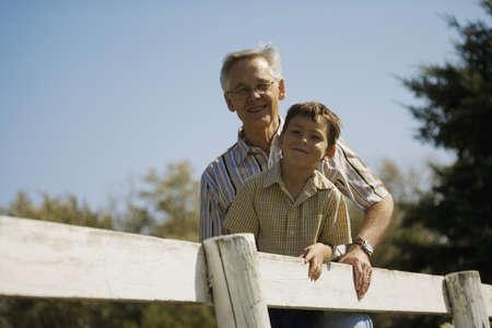 祖父と孫のフェンスに傾いて外