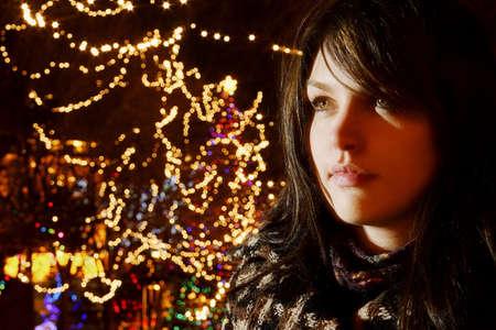Young woman beside Christmas lights
