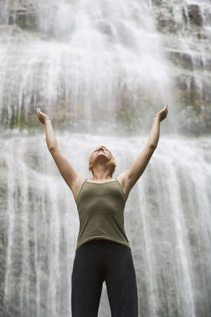 flowing water: Woman with arms raised in front of waterfall