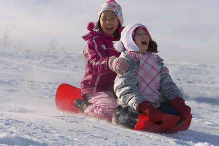 Children tobogganing Stock Photo - 7559357
