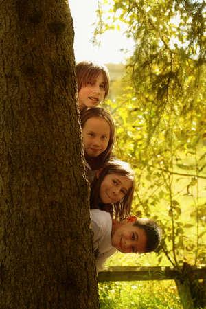 Kinderen zich te verbergen achter de boom stam  Stockfoto